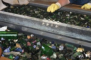 Vor der Schmelze wird Altglas sorgfältig von Fremdstoffen gereintigt - maschinell und per Hand.