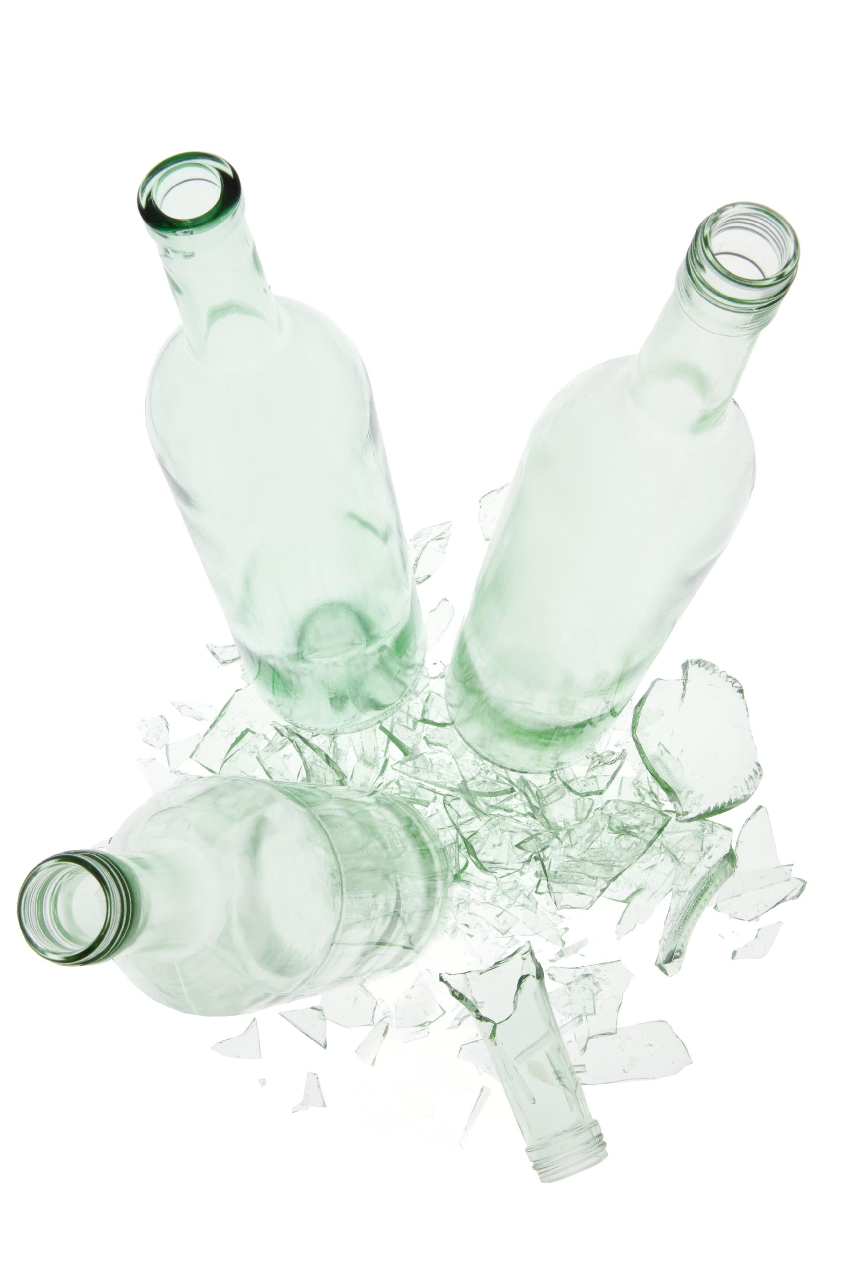 Drei hellgrüne leere Glasflaschen stehen auf den Scherben einer vierten hellgrünen Glasflasche.
