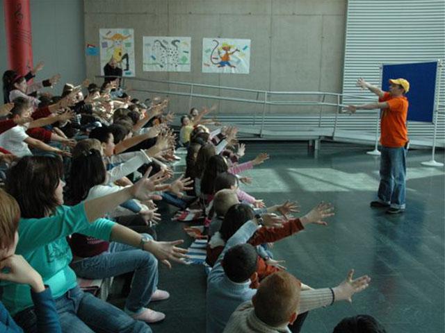 Bobby Bottle vor einer Schulklasse in einem Turnsaal