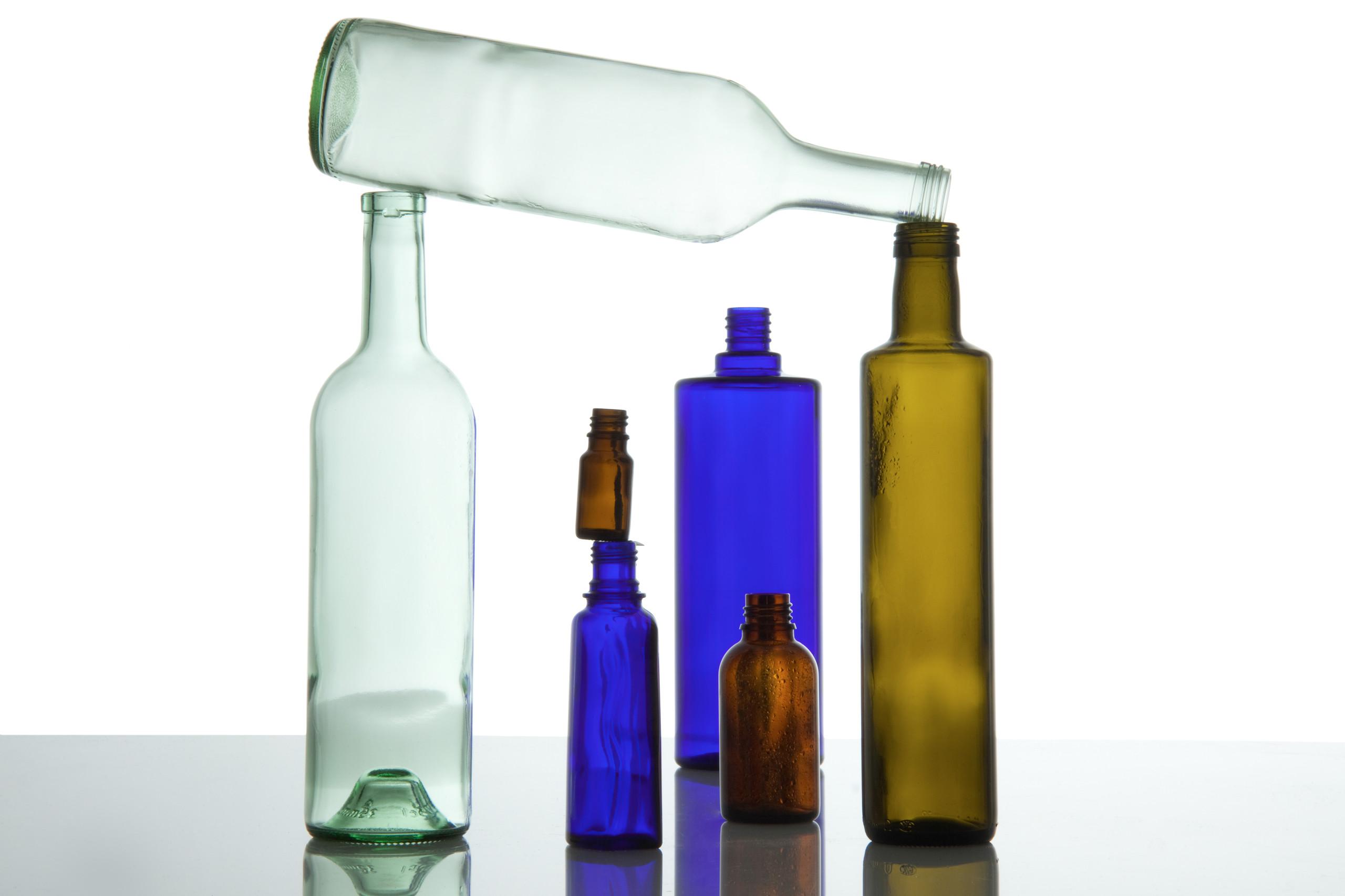 Mehrere farbige Glasverpackungen tragen eine hellgrüne leere Glasflasche, die quer über den anderen liegt.