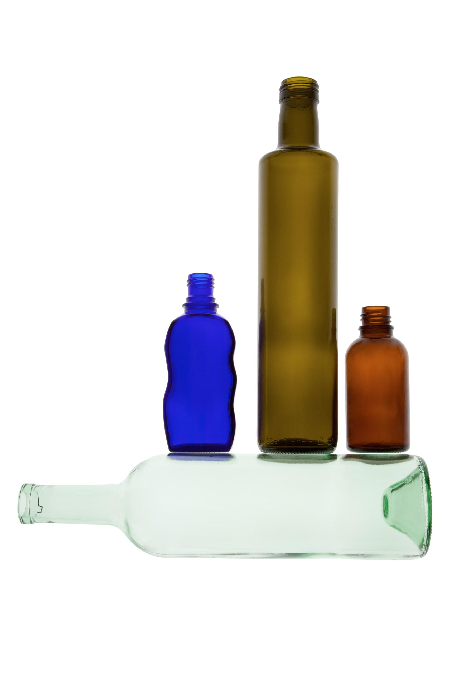 Mehrere gefärbte Glasflaschen stehen auf einer querliegenden hellgrünen Glasflasche.