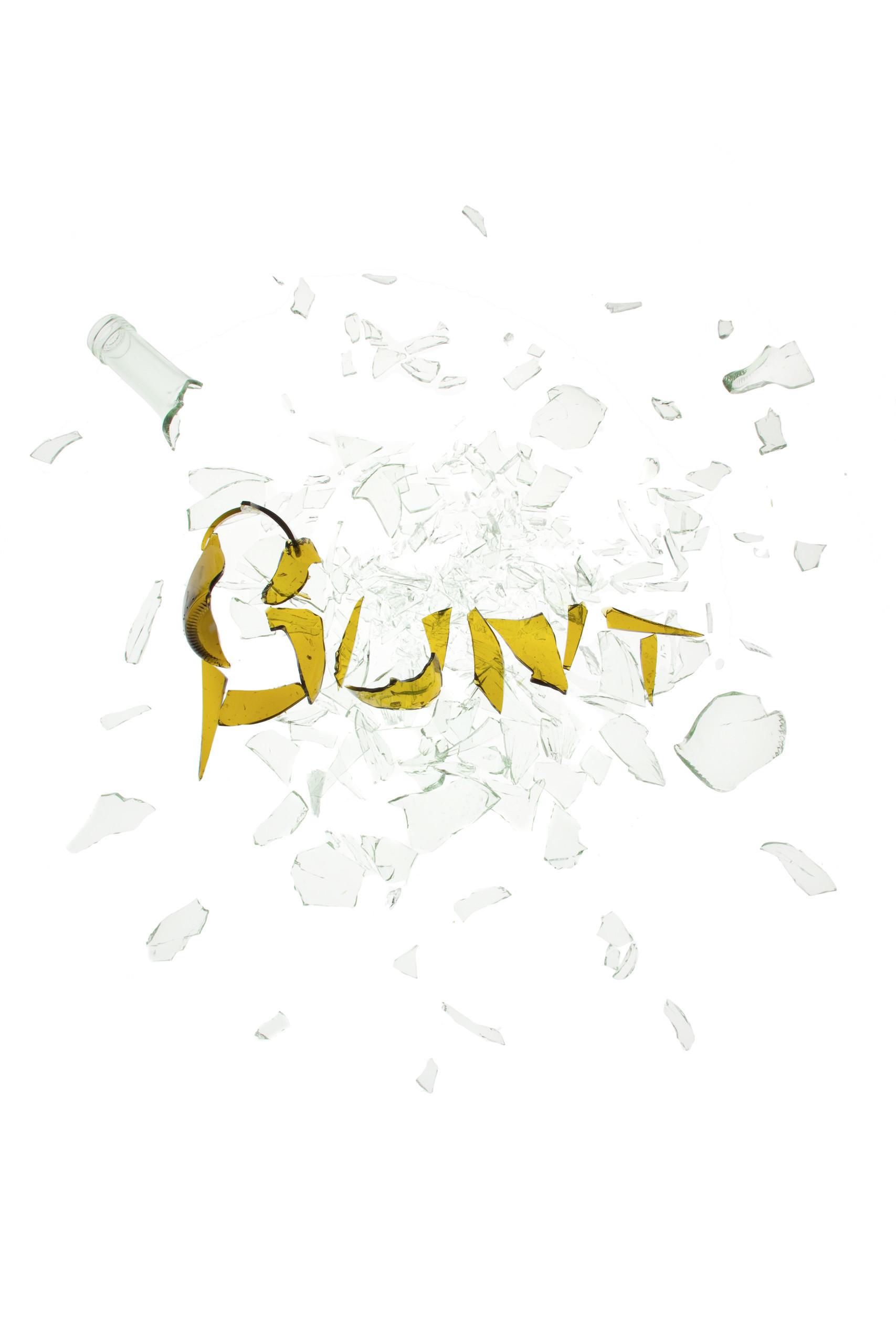 hellgrüne Glasscherben, darauf mit braunen Scherben das Wort 'bunt' geschreiben.