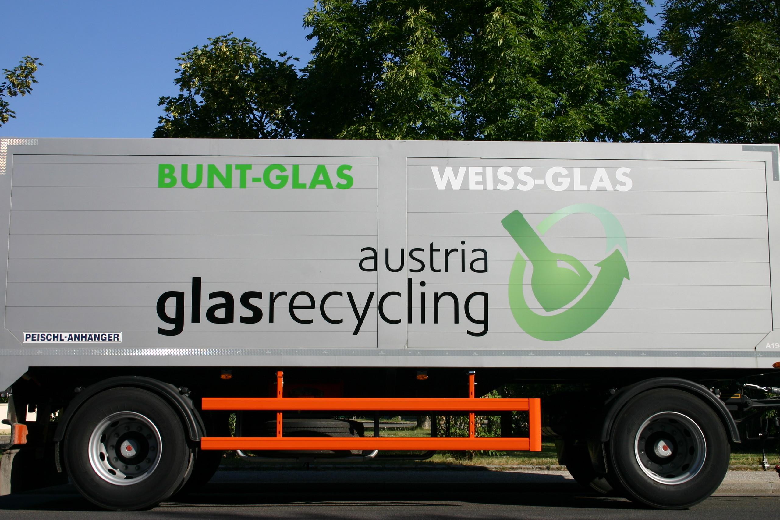 """Der Anhänger eines Glassammel-LKW mit der Beschriftung """"Buntglas"""" sowie """"Weißglas"""" und dem Logo der Austria Glas Recycling, einer grünen Flasche, die von einem grünen Pfeil umkreist wird."""