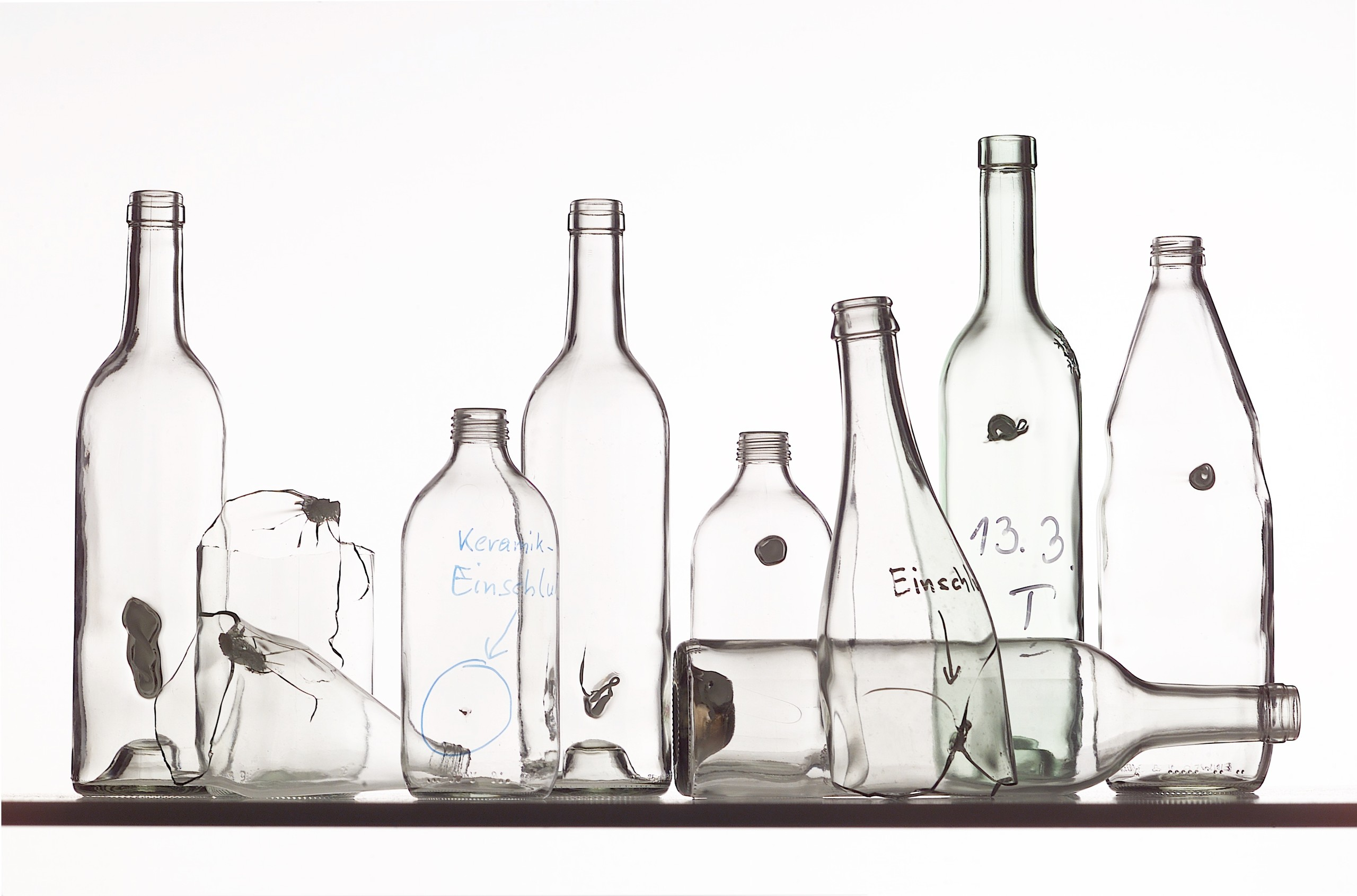 Mehrere durchsichtige Flaschen, die alle fehlerhaft sind, da sie sogenannte Einschlüsse aus anderen Materialien enthalten.