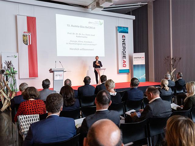 Bild eines Austria Glas ReCIRCLE, Sprecher auf Bühne, davor Publikum