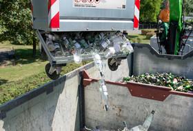 Weißglascontainer wird auf LKW entleert