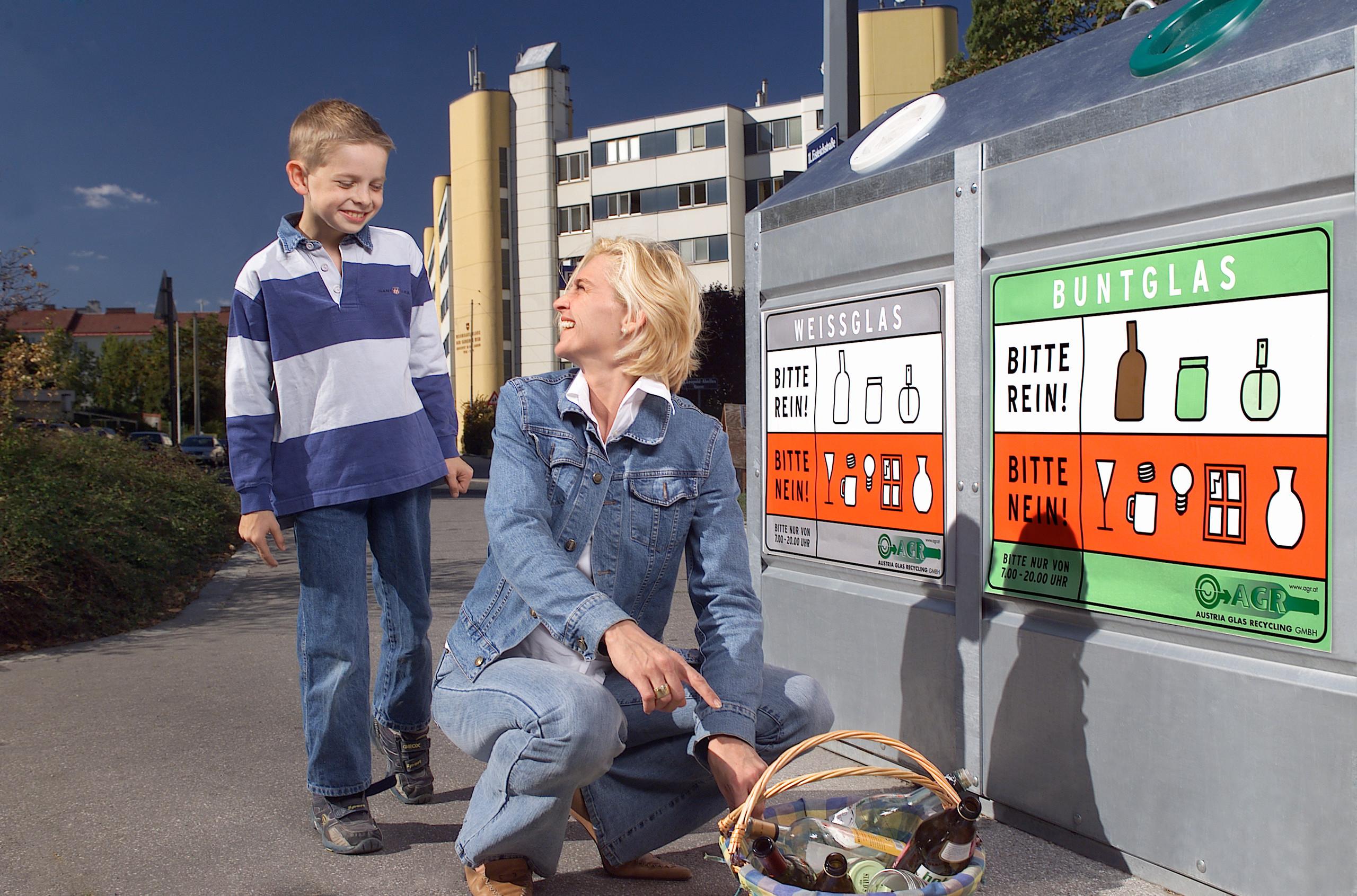 Eine Frau hockt vor einem Altglassammelbehälter neben einem Korb voll Glasverpackungen. Sie wendet sich einem Kind zu, das ihr über die Schulter auf den Korb mit Glasverpackungen blickt. Es scheint, sie erklärt dem Kind etwas.
