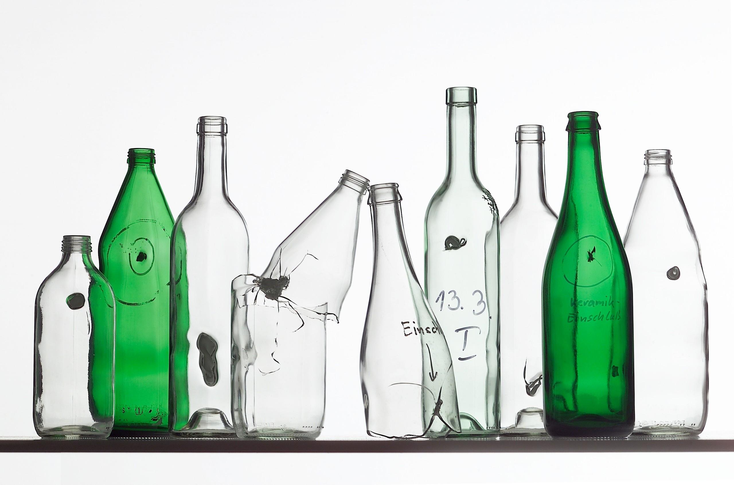 Mehrere durchsichtige und zwei grüne Flaschen, die alle fehlerhaft sind, da sie sogenannte Einschlüsse aus anderen Materialien enthalten.
