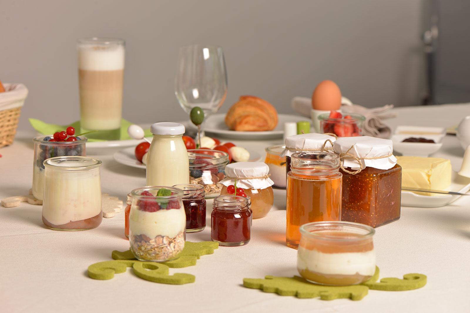 Ein gedeckter Tisch: Honig, Marmelade, Joghurt und andere Köstlichkeiten in Glasverpackungen aden zum Frühstück ein.