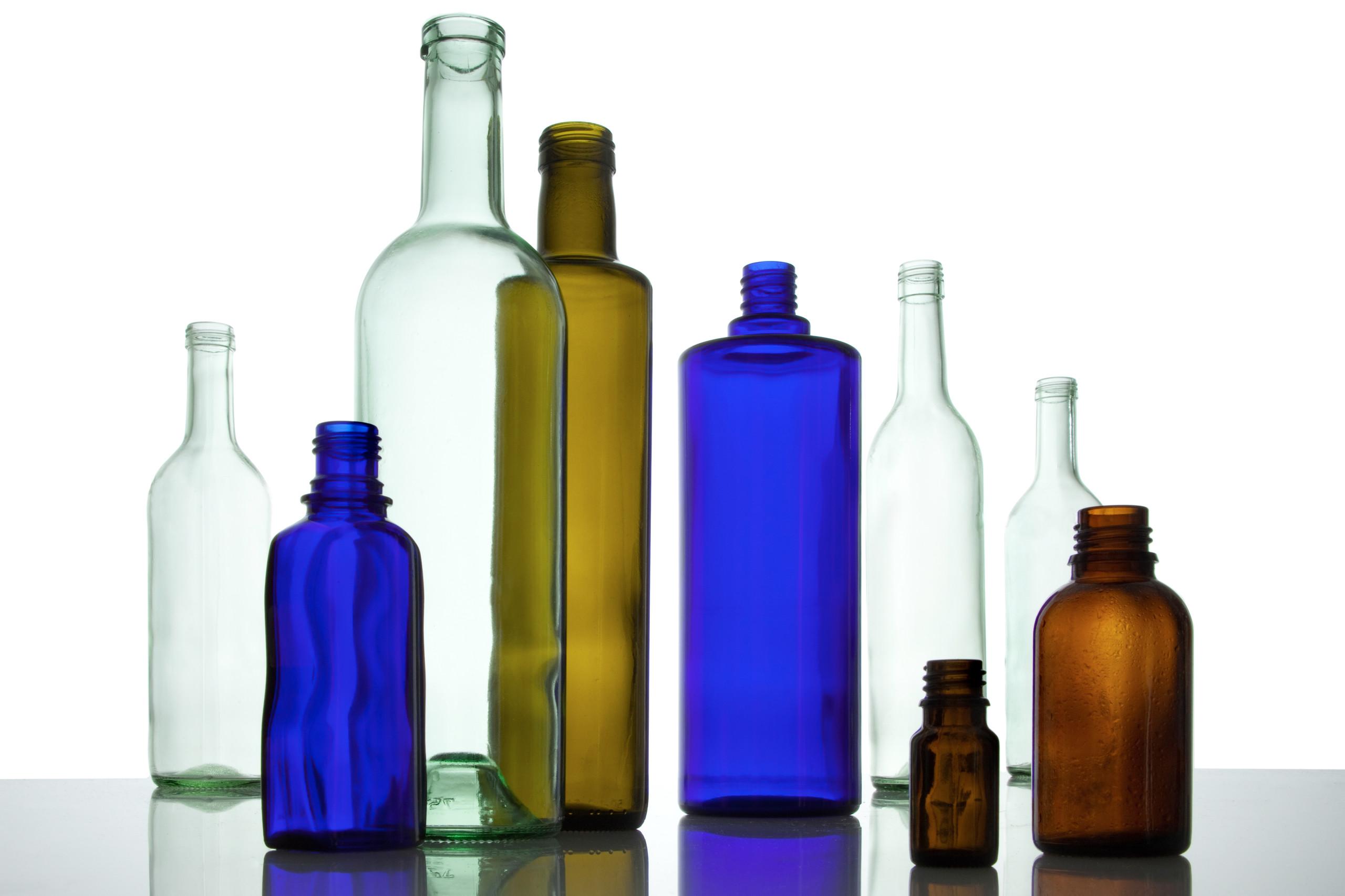 Mehrere leere Glasflaschen in verschiedenen Farben stehen neben- und hintereinander.