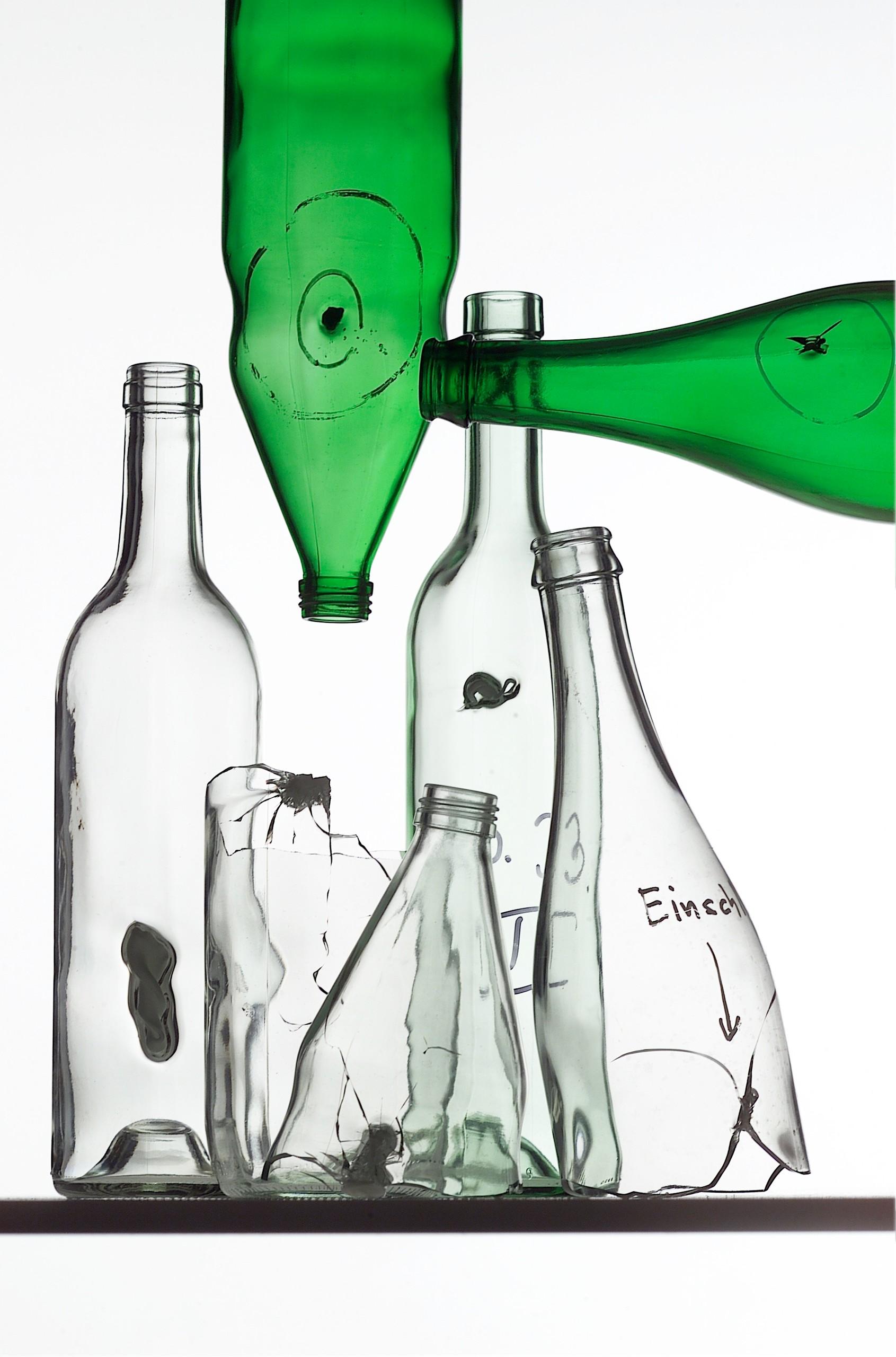 Mehrere durchsichtige Flaschen und zwei grüne, die alle fehlerhaft sind, da sie sogenannte Einschlüsse aus anderen Materialien enthalten.